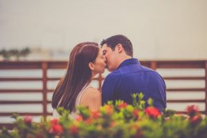 Romantic couple sitting on bench on waterfront and kissing passionately